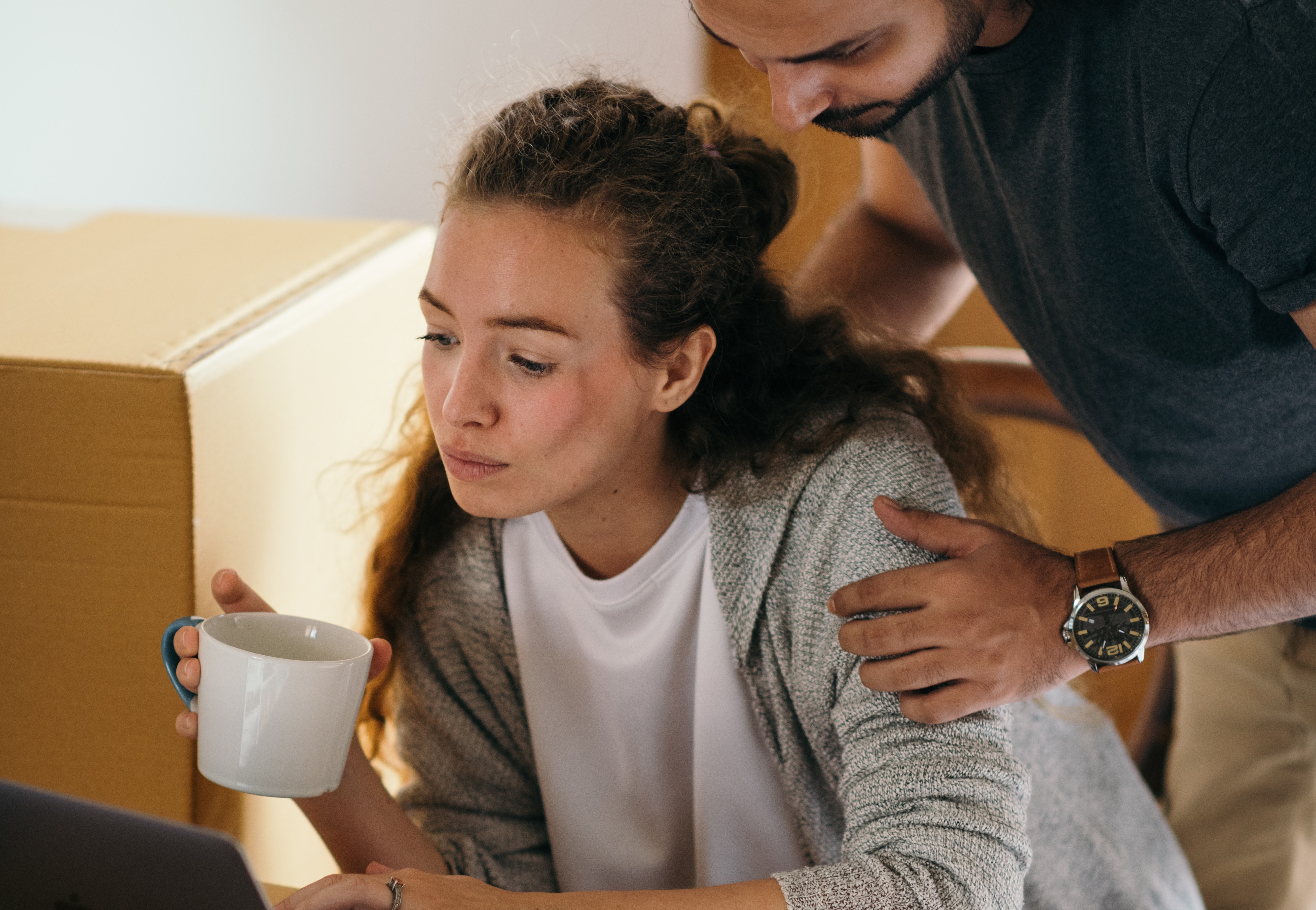 young-couple-using-laptop-in-room-full-of-packed-boxes-4247719